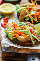 Asian sandwich with fried chicken and fresh vegetables-carrots, cucumber, chili pepper, cilantro and sesame