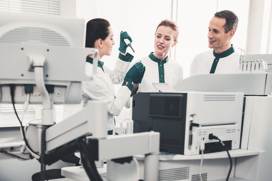 Detecting anomaly. Skilled laboratory scientists using modern hospital equipment and investigating analyses while standing in well supplied hospital