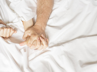 couple hands pulling white sheets in ecstasy, orgasm. Concept of passion. Oorgasm. Erotic moments. Intimate concept. Sex couple. Bedroom. Hotel room. Spa. Vacation.