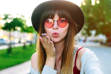 Outdoor portrait of pretty student girl taking a selfie.Beautiful urban woman taking picture of herself, selfie. Filtered image.Pretty hipster girl taking selfie and making duck face. Sending kisses