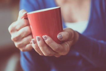 Woman's hands holding a mug of hot beverage
