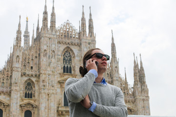 Caucasian tourist speaking by smartphone near Milan Cathedral, Italy. Concept of modern technology, advantageous tariff plan and landmarks.