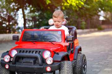 Cute 2 year old boy in a white T-shirt is riding a red jeep in the park