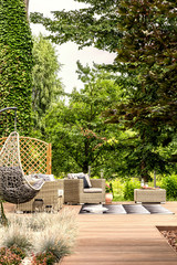 Hanging chair and garden furniture on terrace near trees during summer. Real photo
