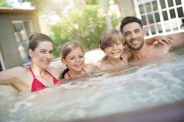 Family of 4 enjoying bath in spa