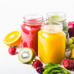 Selection of multicolored fruit smoothies  in glass jars