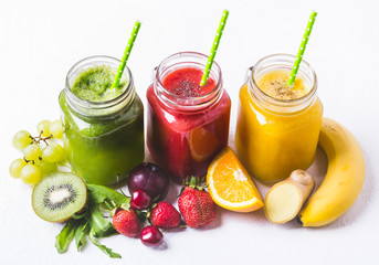 Red, yellow and green smoothie in a glass jar and ingredients on white background