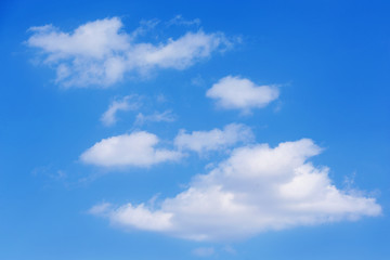 a series of white clouds of different sizes, arranged diagonally, on a blue sky. natural background