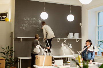 Businesswoman standing on step ladder drawing smiley face on wall while colleagues working at creative office