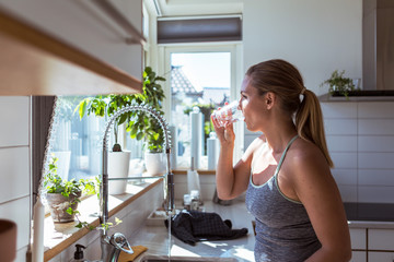 Woman drinking tap water in kitchen
