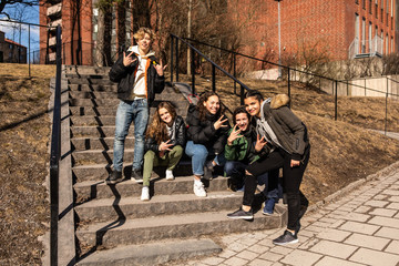 Portrait of cheerful multi-ethnic teenage friends showing hand signs on steps in city