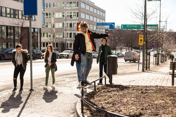 Teenage boy balancing on railing while friends walking on sidewalk in city during sunny day
