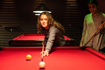 Smiling teenage girl aiming cue ball on illuminated red pool table by friend