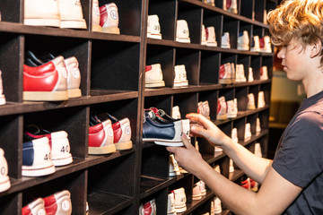 Side view of blond teenage boy holding bowling shoes at wooden rack