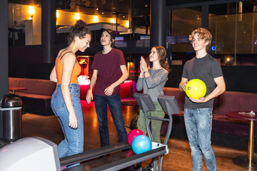 Happy teenage friends standing by rack at bowling alley