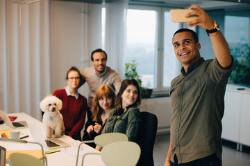 Smiling businessman taking selfie with colleagues at dog at creative office