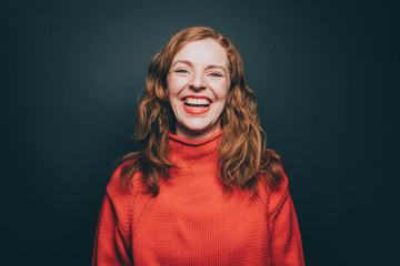 Portrait of woman in orange top laughing against gray background