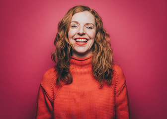 Portrait of smiling woman in orange top against pink background