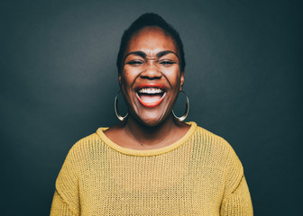 Mid adult woman laughing over gray background