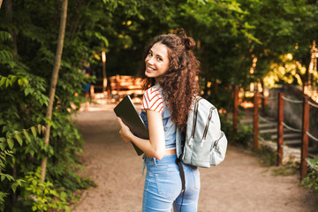 Photo of smiling caucasian woman 18-20 wearing backpack, walking through green park with silver laptop in hands
