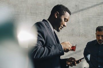 Young businessman using mobile phone while having tea at office
