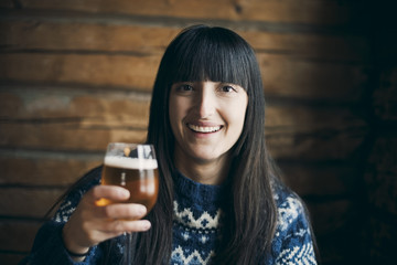 Portrait of smiling woman holding drinking beer glass while sitting at log cabin