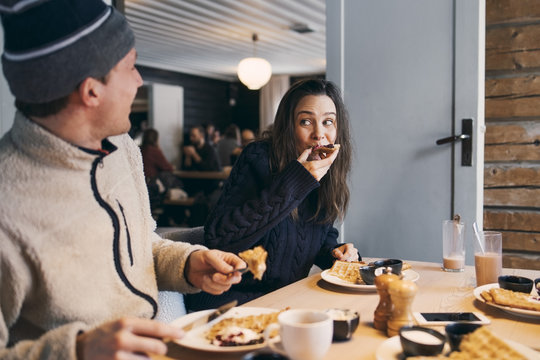 Woman eating breakfast while sitting with friend at table in log cabin