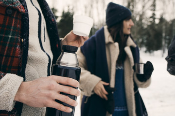 Midsection of man having coffee with friends at park during winter