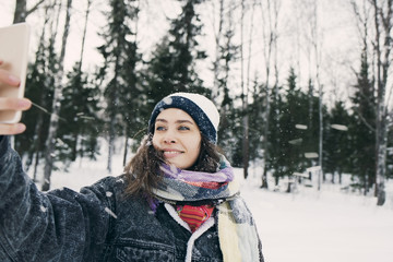 Young woman taking selfie in winter setting