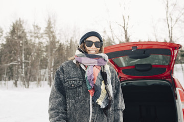 Smiling woman standing by car on snow covered landscape
