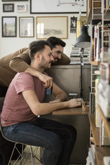 Side view of gay couple shopping online through computer at home
