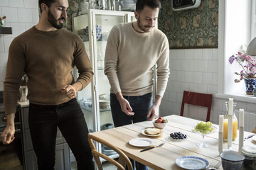 Young couple looking at arranged table while standing in kitchen