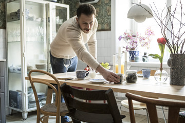 Young man arranging cup on table in kitchen at home