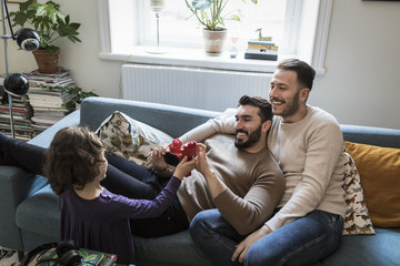 High angle view of daughter showing blocks to smiling fathers in living room