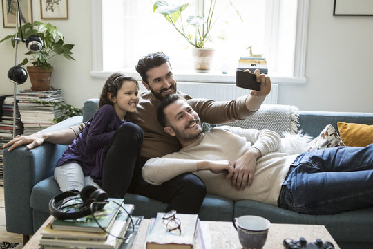 Two men and girl taking selfie at home
