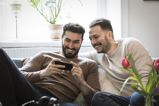 Two men using cell phone on sofa