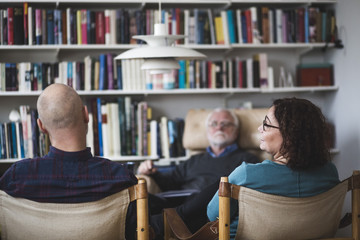 Mature couple talking while sitting with therapist at home office