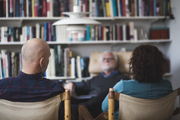 Mature couple discussing with therapist while sitting against bookshelf