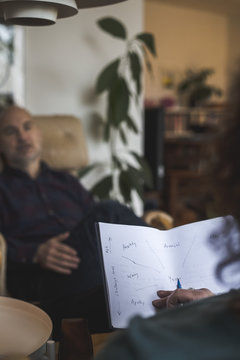 Therapist holding paper while discussing with patient during session