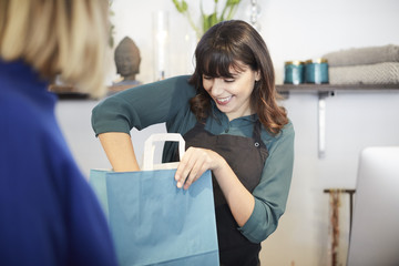 Smiling female owner packing shopping bag for customer at store