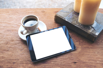 Top view mock up image of black tablet with white blank desktop screen and coffee cup , book , candles on vintage wooden table in cafe