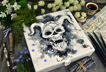 Box with devil face and magic objects with flowers. Occult, esoteric and divination still life. Halloween background with vintage objects and magic ritual