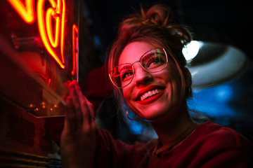 Cheerful woman at neon sign