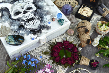 Box with scary demon face, magic mirror, voodoo doll and myctic objects on witch table. Occult, esoteric and divination still life. Halloween background with vintage objects and magic ritual
