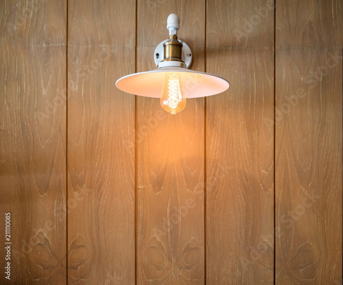 A glowing modern white led lamp on the plank wooden wall simply
