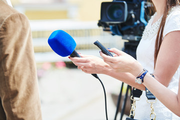 News comment. reporter with microphone making interview