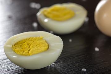 Slices of boiled hard eggs on a dark slate with sea salt