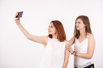 Close up portrait of two beautiful young woman taking a selfie over a white wall in studio