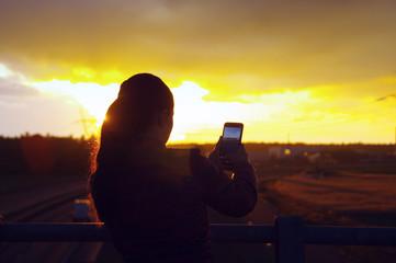 Girl making sunset photo