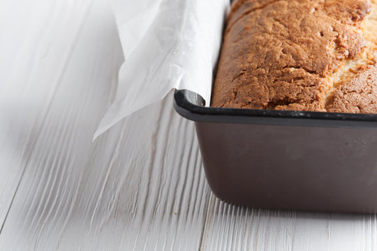 Banana bread in a pan with white parchment paper on a white wooden table. Close up. Bread cracks pattern. Bakery concept